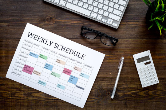 Weekly schedule of manager, office worker, pr specialist or marketing expert. Table with multicolored blocks on dark wooden office desk with computer, glasses, calculator top view