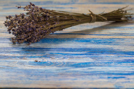 background. bouquet of dry twigs of lavender lies on a white wooden table