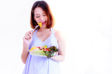 Health concept: Beautiful pregnant woman is eating vegetable by using fork. Gorgeous mother has enjoyed or happiness salad. It is good for health and baby or fetus, isolated on white and copy space.