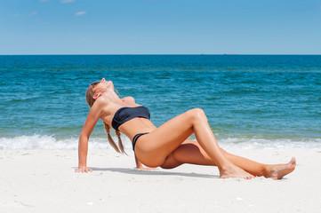 Beautiful slim woman in bikini lying on sand on the beach