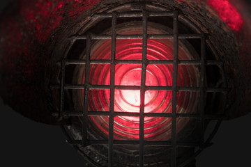 Old and dirty red shunting light at the railway isolated on a dark background, close-up.