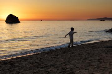 Young boy walking near by the sea at dusk at Prasoudi beach, Corfu Island, Greece