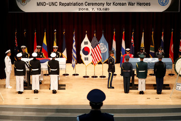 South Korean and United Nations Command (UNC) honor guards stand in front of flag-draped coffins with remains of United Nations Command (UNC) and South Korean soldiers who were killed in North Korea in the 1950-53 Korean War