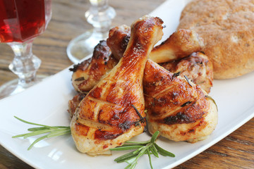 Grilled chicken legs with rosemary served on white plate. Dinner background