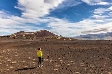 Hiking in Iceland - Adventure travel. Videographer girl tourist on wanderlust walk filming video with camera. Hero landscape shot of desert nature.