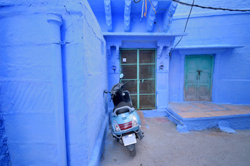 A scooter parked in front of a blue colored house in Jodhpur.