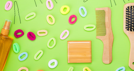 on a light green background, scattered objects to create hairstyles, gum different colors, and a comb, and a spray for styling.