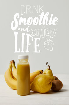 yellow detox smoothie in bottles with bananas, pears and kiwis on white background, drink smoothie and enjoy life inscription