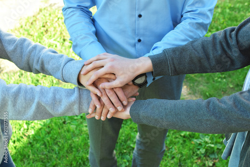 Stack of family people hands on green grass background