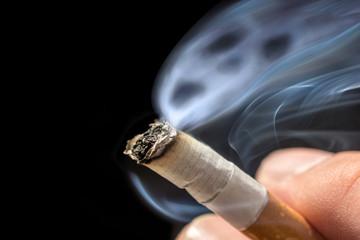 Gefährlicher Qualm aus einer Zigarette vor schwarzem Hintergrund