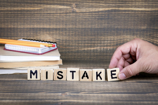 Mistake. Wooden letters on the office desk, informative and communication background