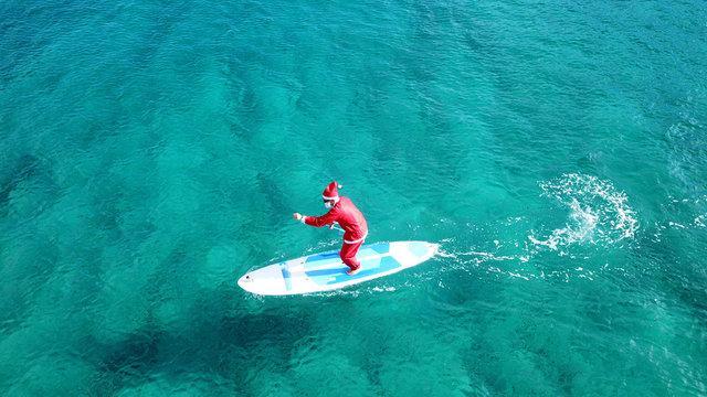 Aerial drone of Santa Claus paddle surfing in Caribbean turquoise clear waters