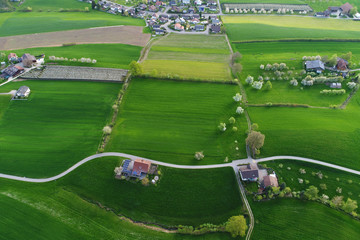 Bright green fields with farms from a bird's eye view on a beautiful spring day in central Switzerland