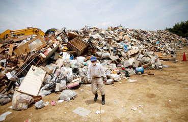 A local resident piles up household waste caused by a flooding at a temporary waste-collection point at Mabi Clean Center in Kurashiki