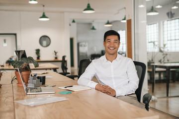Fototapeta Smiling Asian businessman working at his desk in an office obraz