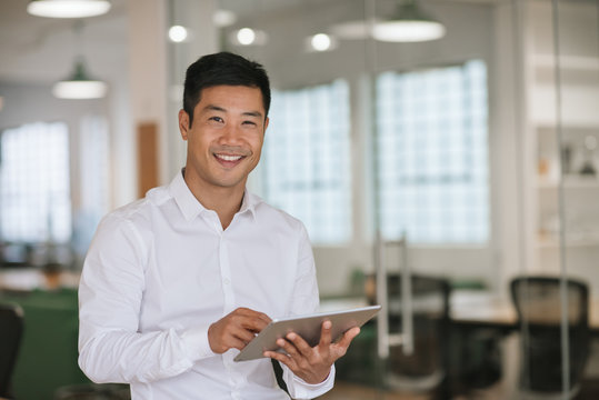 Smiling Asian businessman using a digital tablet in an office