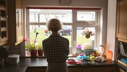 Woman looking through window in the kitchen