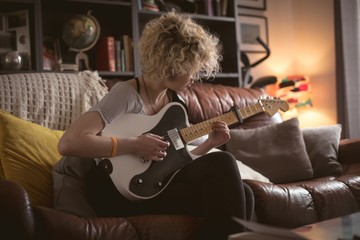 Young woman playing guitar in living room