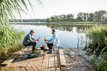 Landscape view on the lake with two male friends sitting together with beer during the fishing process