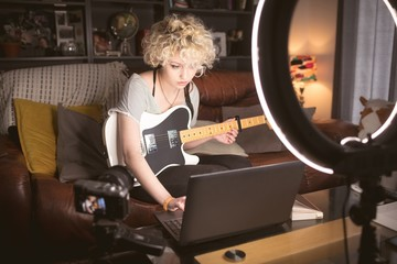 Female blogger with guitar using laptop in living room