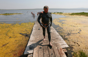 A man, covered with mineral-rich mud, walks while staying at a tourist camp on the bank of Lake Tus in the Republic of Khakassia