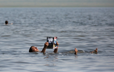 A man reads a magazine as he floats in the salt waters of Lake Tus while staying at a tourist camp in the Republic of Khakassia