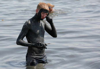 A man covers himself with mineral-rich mud while staying at a tourist camp on the bank of Lake Tus in the Republic of Khakassia