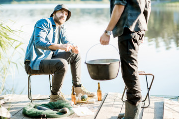 Two fishermen preparing some food during the picnic on the wooden pier near the lake in the morning