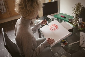 Young woman coloring a sketch