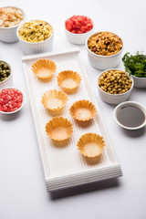 empty Crispy Canape or canapé is a starter recipe from India - Round or square shaped Puri to be Filled with Yogurt and potato , chat, sev, tamarind sauce etc. selective focus