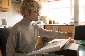 Young woman coloring at home