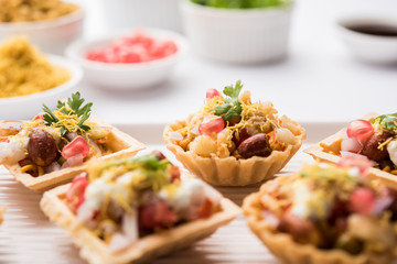 Foto op Aluminium Buffet, Bar Crispy Canape or canapé is a starter recipe from India - Round or square shaped Puri Filled with Yogurt and potato , chat, sev, tamarind sauce etc. selective focus