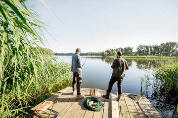 Landscape view on the beautiful lake and green reeds with two men fishing on the wooden pier during the morning light