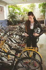 Woman using mobile at bicycle stand