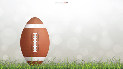 American football ball or rugby football ball on green grass court with light blurred bokeh background. Vector.