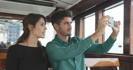 Traveler taking ferry in Hong Kong and using mobile phone to take photo