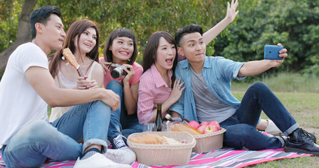 Friends go picnic together in the park and take photo selfie with mobile phone