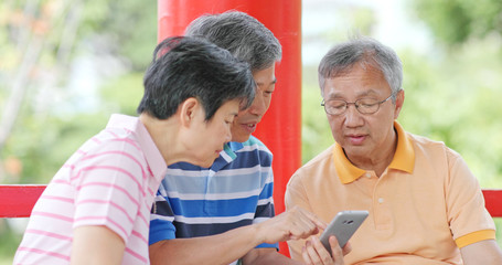 Senior friends talk together look at mobile phone at outdoor park