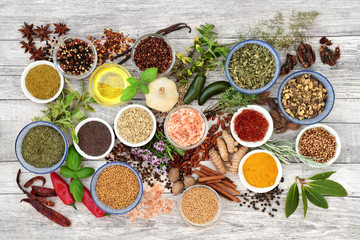 Spice and herb seasoning with fresh and dried herbs and spices with olive oil on rustic wood background. Top view.