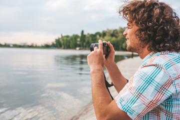Image of young handsome male with curly hair checking photos of nature on his digital camera. Young handsome man wears casual shirt, with digital camera posing in the park. People, travel, lifestyle