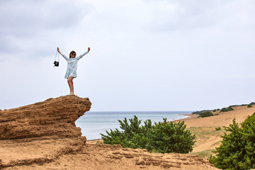 A young woman stands on a rock against a background of blue sea, yellow sand and sky with clouds and admires nature, enjoying solitude