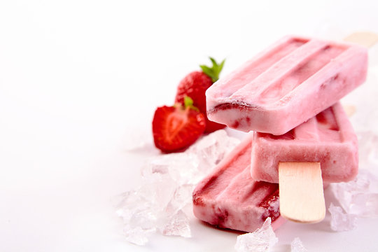 Three frozen popsicles with strawberry ingredients