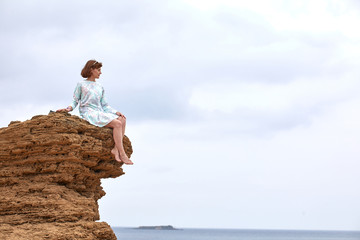 Young woman sits on a rock against the blue sea, yellow sand and sky with clouds and admires nature, enjoying solitude