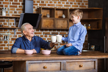 Cheerful man having breakfast with his grandson