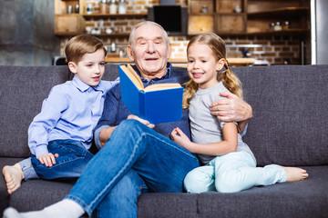 Positive retired man reading a book for his grandchildren