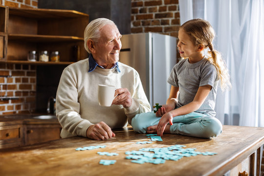 Joyful aged man assembling jigsaw puzzles with his granddaughter
