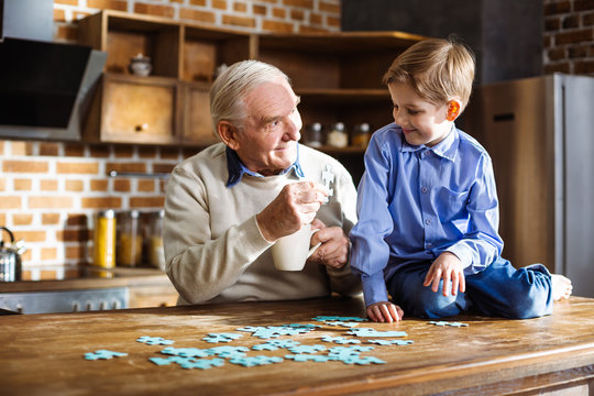 Positive aged man assembling jigsaw puzzle