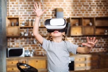 Positive little girl testing VR glasses