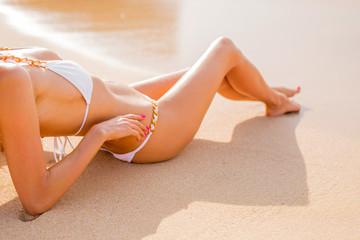 Sexy woman in bikini tanning on the beach