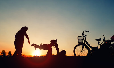 Silhouettes of happy sitting at the park in the evening. with sun flare. Concept of friendly family.